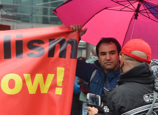 A man under a pink umbrella talks to a man whose back is to the camera - May day, International Workers Day rally at Dundas Square on a rainy day -