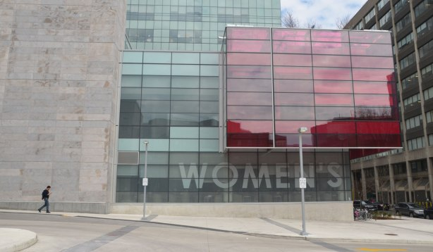 a lone man walks by the new Womens College Hospital building with its light grey stone facade, large glass section, and large pink glass section.