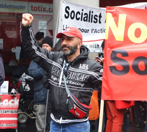 May day, International Workers Day rally at Dundas Square on a rainy day - a man holds his fist in the air as he stands beside a banner