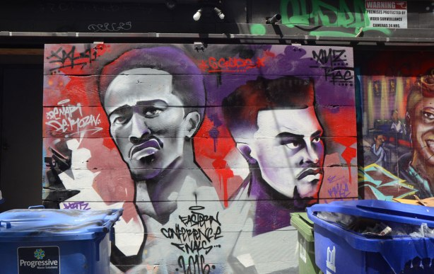 streetart mural in tribute to Toronto Raptors basketball team and their presence in the Eastern Conference Finals in 2016. The heads of two black basketball players on a red and purple background.