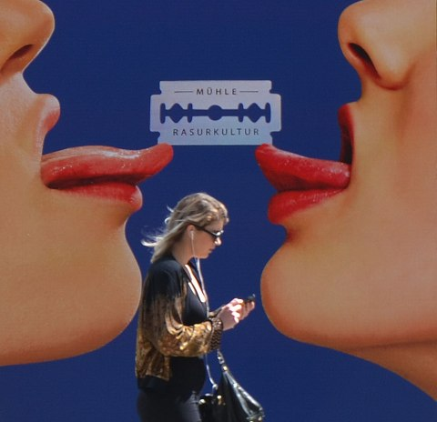 A woman with her phone in her hands walks past a large poster of two women face to face where all you can see is their nose, mouth, chin and tongues that are stuck out. A razor blade balances between the two tongues.