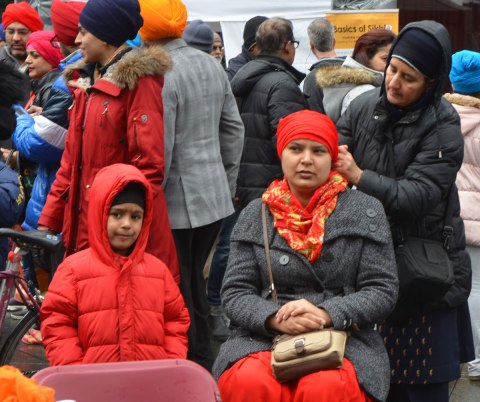 People having their heads wrapped in a turban, many different colours, at an event at Yonge Dundas square run by the Sikh Youth Federation. Sikh volunteers are making the turbans using stacks of fabric laid out on 5 long tables. A woman gets a red turban while her son looks on