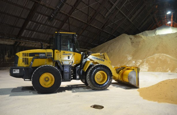 a large yellow front end loaded is parked inside a warehouse. A large pile of raw sugar is in the background.