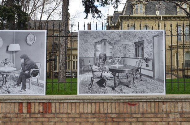 photos mounted along the exterior of a wrought iron fence around the Italian Consulate, right beside the sidewalk. The consulate is on old brick house (mansion) from the 1800's - the photos are of refugees that have been photoshopped into old photos of the interior of the apartment of a wealthy person from the 1920's
