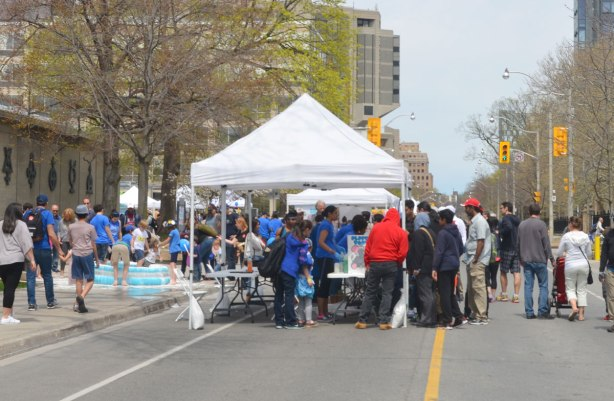 looking up St. George street on the downtown University of Toronto campus. A white tent is set up on the street and under the tent are students running science demonstrations.