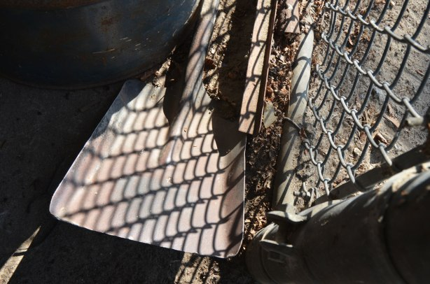 the end of a shovel is in the ground, behind a chainlink fence. The sun is shining and making reflections. The reflection of the chainlink fence is on the shovel.
