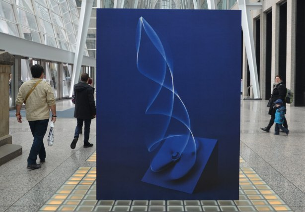 "A picture taken inside the Allan Lambert Gallery at Brookfield Place, photos by Sjoerd Knibbeler, a series called Current Study large pictures standing in the middle of the gallery, as well as series called ""Paper Planes"" which are hung from the ceiling"