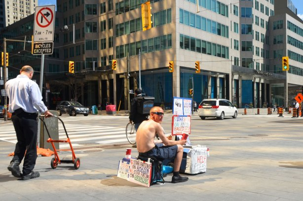 a shirtless man in sitting on a stool at the corner of Front and Union streets. He has four signs (behind, above, in front, and beside him) asking for spare change or for you to buy his novel that is well rated on both Amazon and Goodreads.