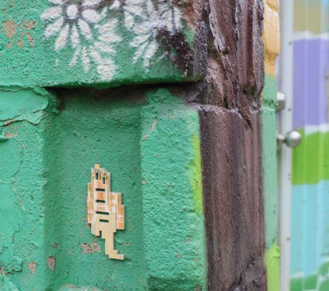 a little wooden stikman with only one leg on a green concrete block wall, with white stencilled daisies above him, street art in an alley