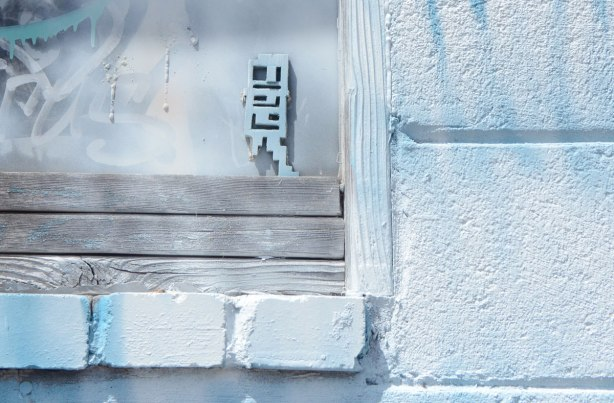 a very pale blue stikman on a very pale blue window and wall.