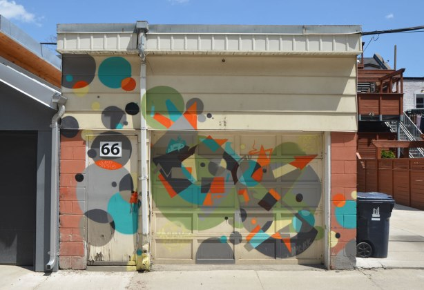 number 66 in a lane, garage door, door and walls covered with circles and triangles in different colours.