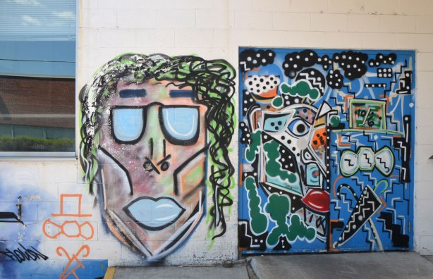 A door covered with a very abstract face painting and another graffiti face beside the door.