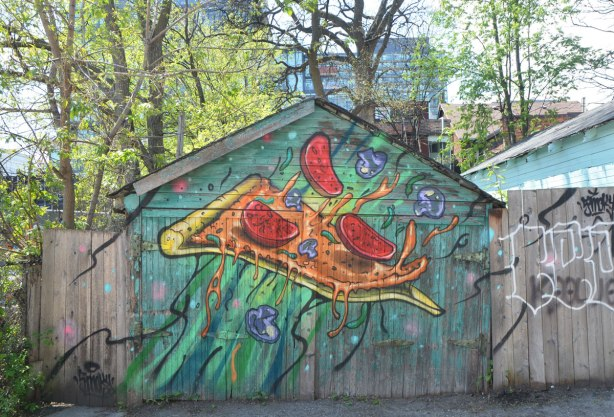 An old wood garage in an alley that is painted by Shalak, a slice of pizza with pepperoni pieces flying off it (or onto it!)