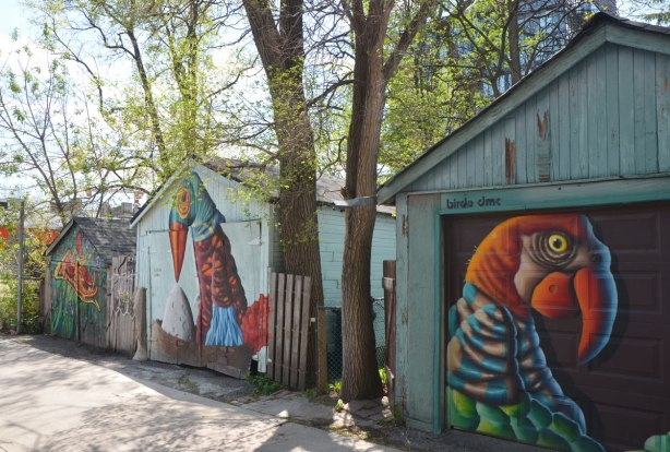 Three garages in an alley, with trees growing between them. The first two have garage doors with birdo murals on them and the third has a pizza street art painting by Shalak