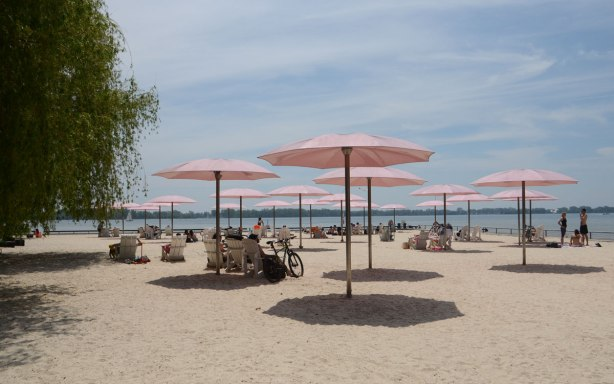 people sitting on white chairs under pale pink umbrellas at Sugar Beach. sand, water and blue sky, beside Lake Ontario
