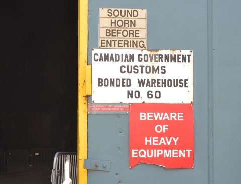 "three warning signs on the outside of a door of the Redpath Sugar shed, a warehouse for storing raw sugar. One says ""Beware of Heavy Equipment"", the second says ""Sound horn before entering"" and the third says ""Canadian Government Customs Bonded Warehouse no. 60"""