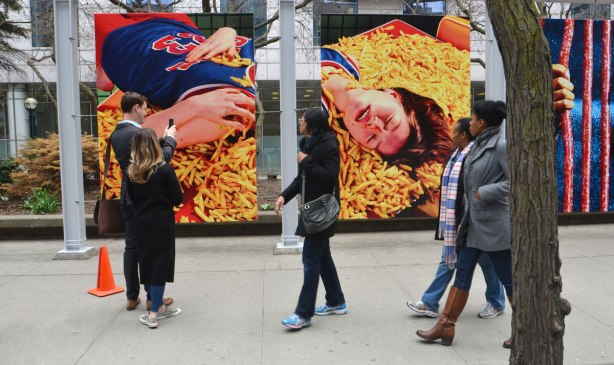 People walk past two large posters that show a girl lying on a large pile of french fries.