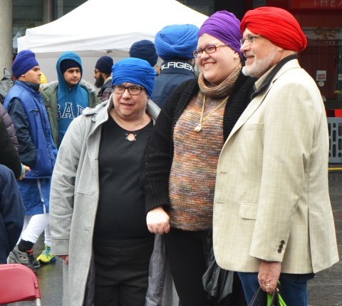 People having their heads wrapped in a turban, many different colours, at an event at Yonge Dundas square run by the Sikh Youth Federation. Sikh volunteers are making the turbans using stacks of fabric laid out on 5 long tables. Three people pose to have their picture taken after getting turbans