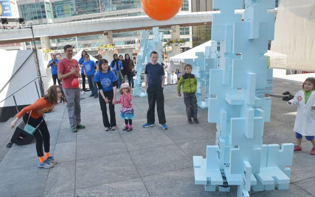 A young girl throws a large orange ball at a tower of polysyrene blocks in an attempt to knock it over, an activity at Science Rendezvous on the stage at Dundas Square.