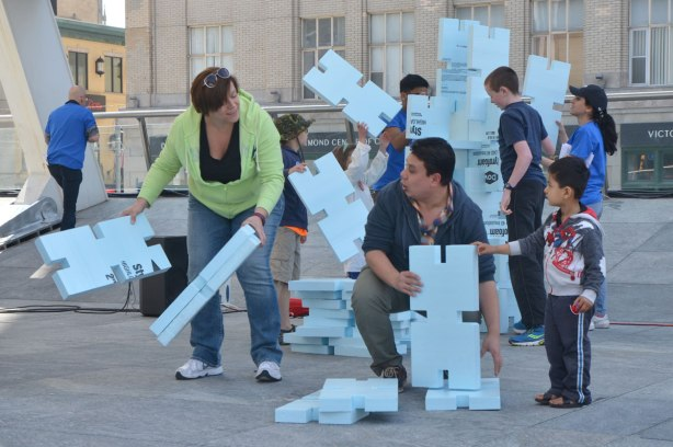 competition to build the highest, strongest tower out of hard styrofoam blocks, children and adults working together.