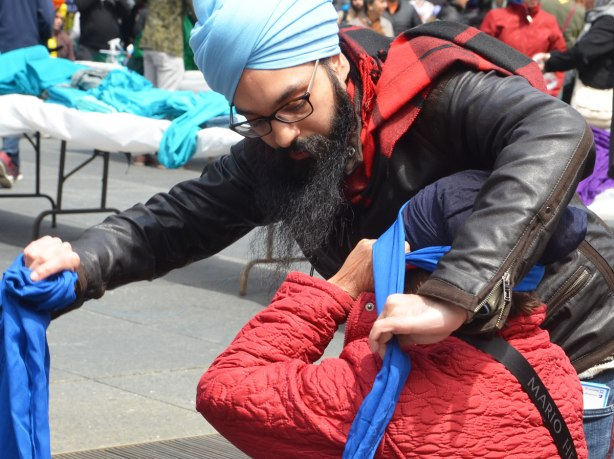 a man is wrapping a seated woman's head with a blue turban