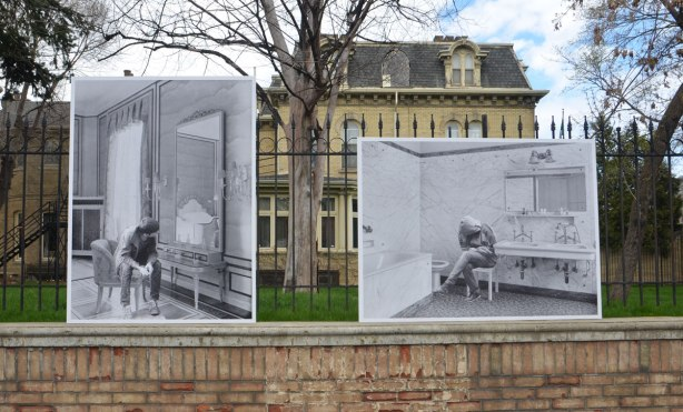 photos mounted along the exterior of a wrought iron fence around the Italian Consulate, right beside the sidewalk. The consulate is on old brick house (mansion) from the 1800's - phot by Jens Ullrich of a woman refugee with her face obscured by clothing, sitting on a chair in the bathroom of a large bathroom. also a photo of a male refugee in another room, looking in a large mirror