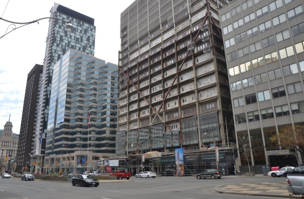 Tall office building is having its concrete facade replaced with glass. The upper floors are still concrete, the middle floors are bare and the lower floors have new glass
