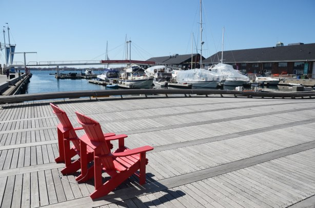 Two red Muskoka chairs sit on the Wave Deck at the waterfront in Toronto. Boats in the harbour are in the background, some with plastic wrap still on them from winter storage.