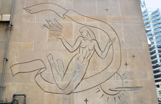 outline drawing of a woman floating in the sky, incised into limestone facade of a building. She is releasing a bird.