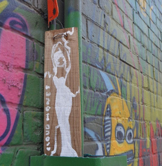 small vertical drawing of a woman, drawn in white, wearing a long form fitting dress, standing, on brown, tied to a wall with a mural laready painted on it.