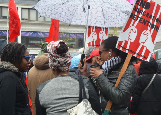 "women talking and laughing together at a rally, holding placards that say ""End Immigration Detention "" and also holding umbrellas"