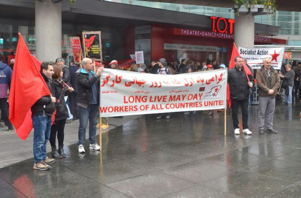 "A group of people holding a large rad and white banner with most of the words written in Arabic and English. The English part says ""Long Live May Day. Workers of all countries unite"""