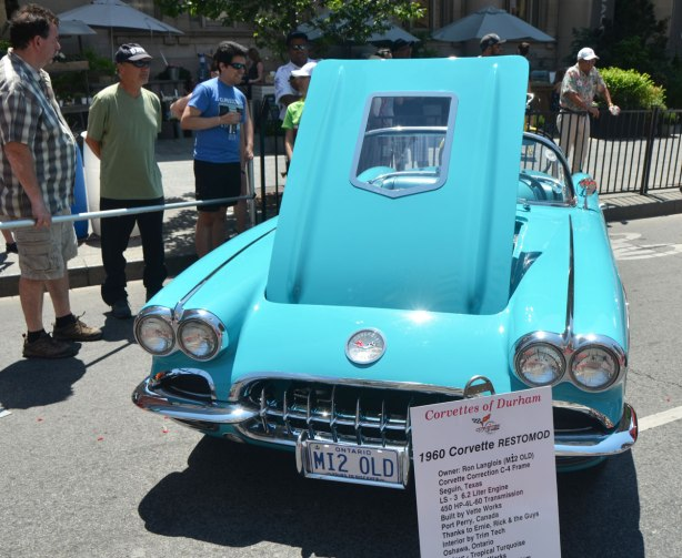 Four men are looking at a turquoise 1960 Corvette at an outdoor car show. it has its front hood open and a sign by its front bumper says that it belongs to Corvettes of Durham