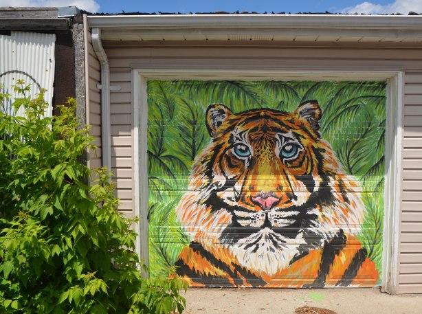graffiti street art animals painted on garage door in an alleyway - a tiger's head