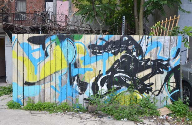 a wood fence with a graffiti painting of a black alligator or crocodile on it. in an alley