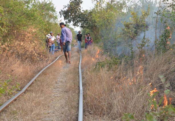 people walking along old train tracks, small fires burn in the bush beside the tracks.