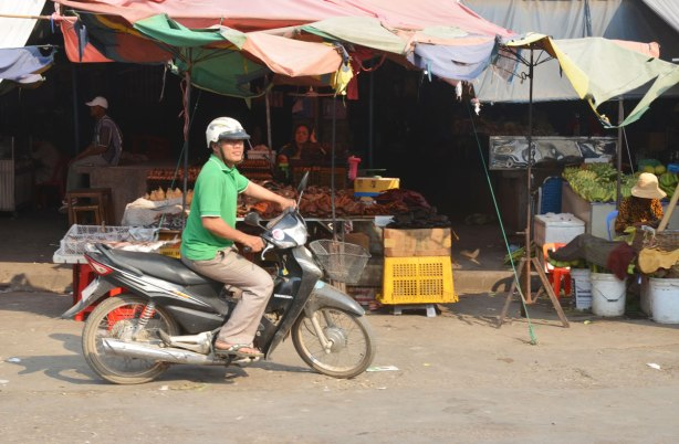 a man on a motorcycle in front of an outdoor store