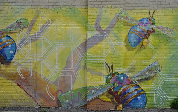 part of a large mural on a wall in a lane, three very big bees