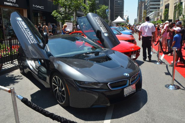 A black BMW i8 electric car with its front scissor doors open.