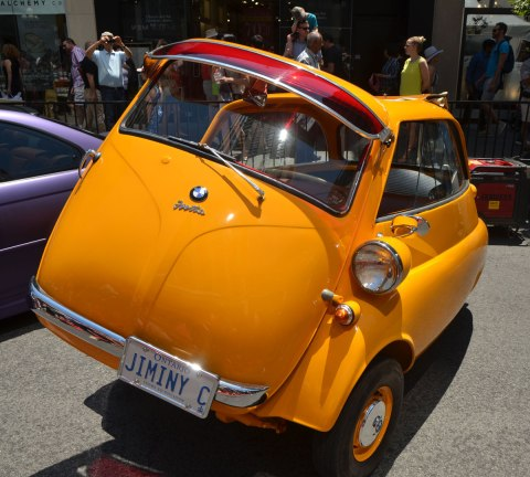 a yellow 1959 BMW Isetta 300 with its front door open - the front of the car opens up, parked on Bloor street for the Yorkville exotic car show.
