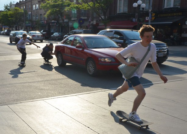 Two young men on skateboards are passing by, another is holding onto the back bumber of a red car while he is on a skateboard and the car is moving.