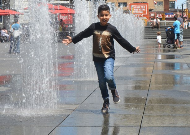 a boy runs down the middle of the fountains at Dundas Square with his arms out at his side and a smile on his face