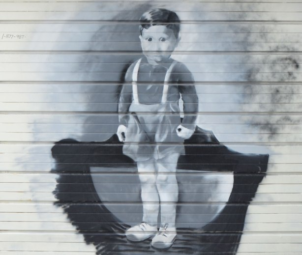 a painting in grey tones of a young boy in old fashioned shorts and long sleeved top, standing.