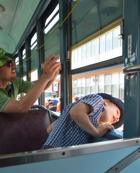 A young boy wearing a hat looks out the window of an old restored streetcar while his father takes a picture out the window
