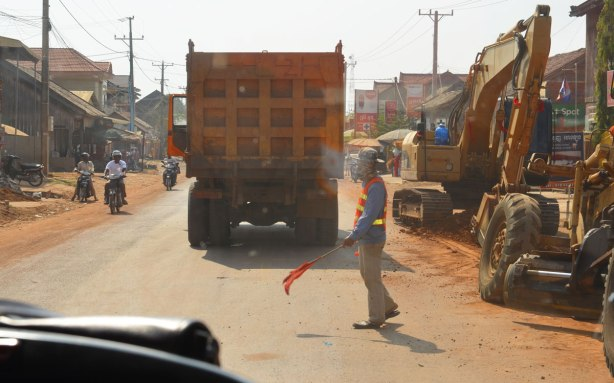 a man with an orange flag controls traffic in a construction zone on the road to Kampong Cham, diggers and dump truck too