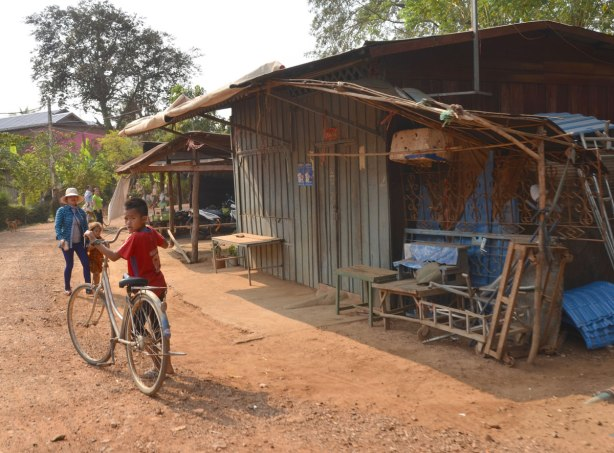 a boy stands beside a bike, holding its handle bars, it is much too big for him, on a dirt road by a wooden building