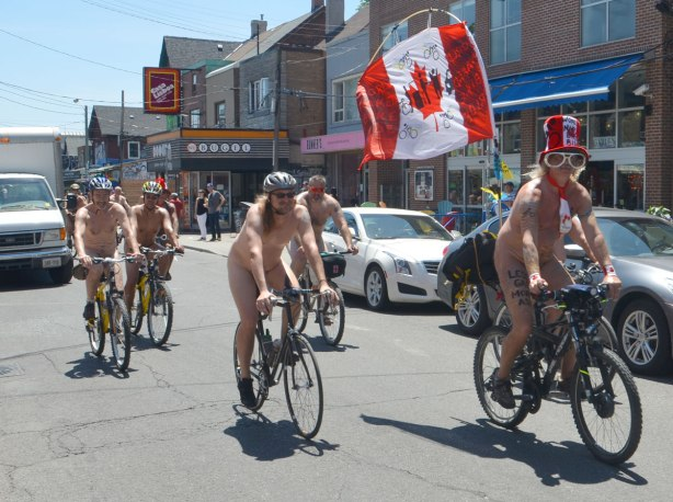 Five or six men on bicycles on a street in Kensington, they are all naked. One is wearing a large Canada Flag hat and has a Canadian flag flying from the back of his bike. Participants in the World Naked Bike Day.