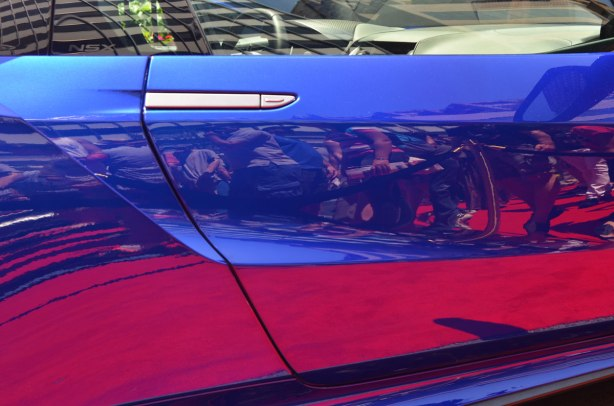 reflections of a crowd at an exotic car show in the side panel of a bright blue car. The people are standing on a red carpet which comes out a magenta colour in the reflection.