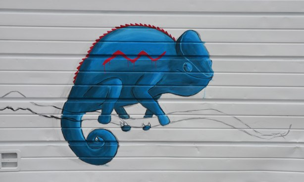 graffiti street art animals painted on garage door in an alleyway - a bright blue chameleon