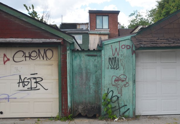 from a lane, two garages, a wood fence painted faded green between the garages, the tops of the houses can be seen behind.